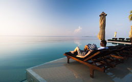 Couple relaxing in luxurious tropical hotel by the pool Royalty Free Stock Photo