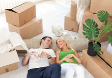 Couple relaxing in the middle of boxes Royalty Free Stock Images