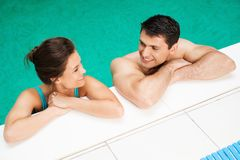 Couple relaxing near swimming pool Stock Photo