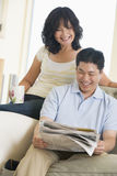 Couple relaxing with a newspaper and smiling Stock Image