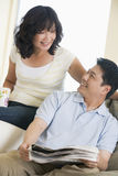 Couple relaxing with a newspaper and smiling Stock Photography