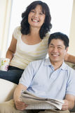 Couple relaxing with a newspaper and smiling Royalty Free Stock Images