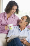 Couple relaxing with a newspaper smiling Stock Photo