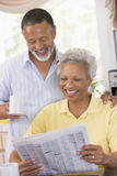 Couple relaxing with a newspaper smiling Stock Photography