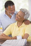 Couple relaxing with a newspaper smiling Stock Images