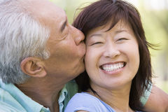Couple relaxing outdoors in park kissing Stock Photos