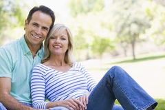 Couple relaxing outdoors in park smiling. At camera Stock Photography