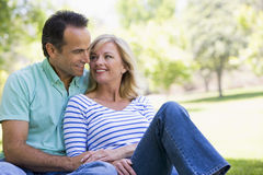 Couple relaxing outdoors in park smiling. Looking away from camera Stock Images