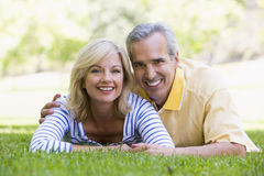 Couple relaxing outdoors in park smiling Stock Photo