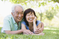 Couple relaxing outdoors in park smiling Royalty Free Stock Photography