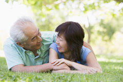 Couple relaxing outdoors in park smiling Stock Photos