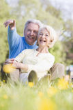 Couple relaxing outdoors pointing and smiling Royalty Free Stock Images