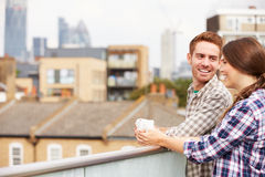 Couple Relaxing Outdoors On Rooftop Garden Drinking Coffee stock images
