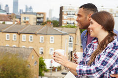 Couple Relaxing Outdoors On Rooftop Garden Drinking Coffee Royalty Free Stock Photos