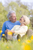 Couple relaxing outdoors smiling. At each other Stock Images