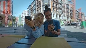 Couple relaxing on outdoors terrace cafe. Friends or couple sit on outside terrace in hip trendy cafe in summer town, waiting for order food on their smartphones stock footage