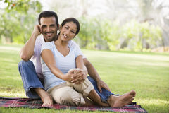 Couple relaxing in park. Sitting on blanket Royalty Free Stock Photo
