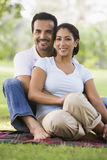 Couple relaxing in park. Sitting on blanket Royalty Free Stock Photography
