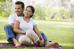 Couple relaxing in park. Sitting on blanket Royalty Free Stock Images