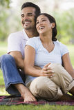 Couple relaxing in park. Sitting on black Stock Image