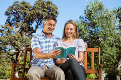 Couple relaxing in the park on bench Stock Photo