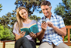 Couple relaxing in the park on bench Royalty Free Stock Photo