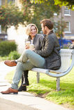 Couple Relaxing On Park Bench With Takeaway Coffee Royalty Free Stock Image
