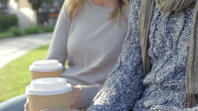 Couple Relaxing On Park Bench With Takeaway Coffee stock footage