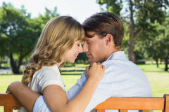 Couple relaxing on park bench together head to head Stock Images