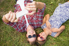 Couple relaxing in the park taking selfie Stock Images