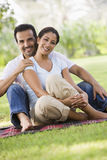 Couple relaxing in park together. Sitting on blanket Royalty Free Stock Photos