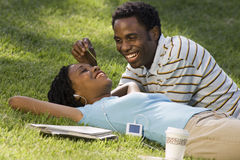 Couple relaxing in park, woman listening to MP3 player, man tickling nose with blade of grass. Couple relaxing in park, women listening to MP3 player, men Stock Image