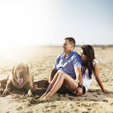 Couple relaxing with pet dog on the beach. Royalty Free Stock Images