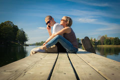 Couple relaxing on a pier Stock Photo