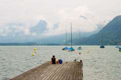 A couple relaxing on  a pier on a mountain lake Stock Photography