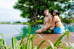 Couple Relaxing By Pool Stock Photo