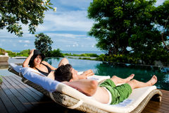 Couple Relaxing By Pool stock images