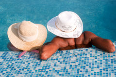 Couple relaxing by the pool Stock Photo