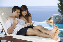 A couple relaxing by a pool Royalty Free Stock Images