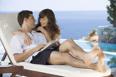 A couple relaxing by a pool Royalty Free Stock Photography