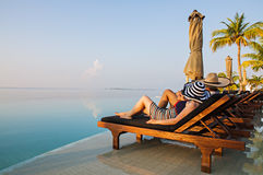 Couple relaxing by the pool in tropical hotel, Maldives Stock Photography