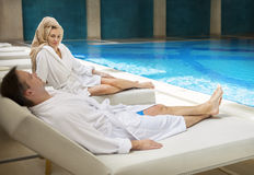 Couple relaxing by the poolside wearing toweling robes Stock Photo