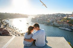 Couple relaxing on Porto in front of the skyline at sunset time stock photos