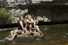Couple relaxing on a rock in the river Royalty Free Stock Photography