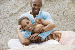 Couple relaxing on rocky beach, woman lying in man's lap, smiling, portrait royalty free stock image