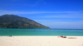 Couple relaxing on sand beach to get tan at Koh Lipe Royalty Free Stock Photo