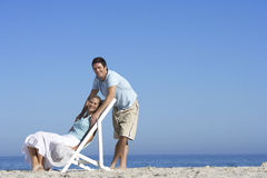Couple relaxing on sandy beach, man standing behind woman in deckchair, smiling, portrait Stock Photo