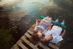 Couple relaxing by side of lake. Overhead view of young couple lying on wooden pier at side of lake Royalty Free Stock Photo