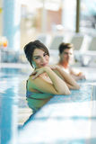 Couple relaxing by the side of the pool Stock Photo