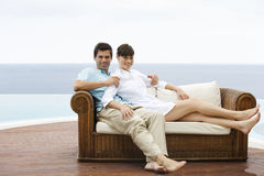 A couple relaxing on a sofa stock photography